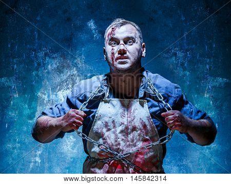 Bloody Halloween theme: crazy killer as bloody butcher vomiting iron chains on dark blue background