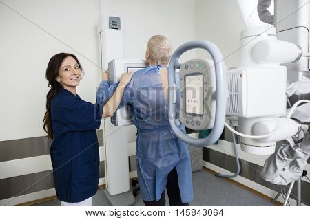 Portrait Of Female Radiologist Taking Xray Of Man