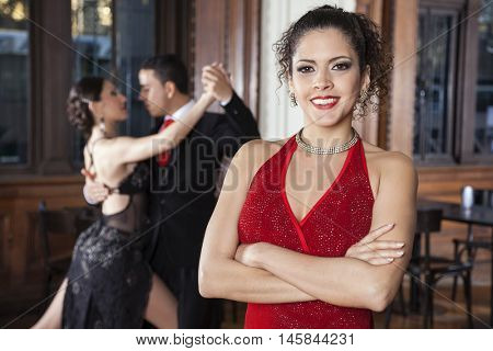 Confident Woman With Arms Crossed Standing While Dancers Doing T