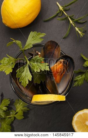 cooked scottish mussels with parsley and lemon in a glass on slate