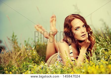 Pretty happy girl lying on a grass on a summer day. Smiling young woman with bright foxy hair outdoor. Holidays, summer vacation.
