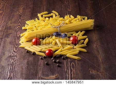 Pasta with different types of italian pasta. Uncooked pasta on the table. mixed dried pasta selection and cherry tomatoes basil sweet peas