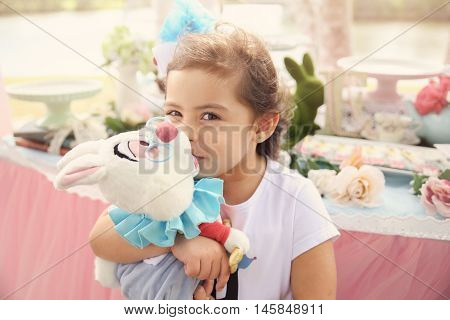 Cute girl with rabbit Alice in wonderland tea party theme