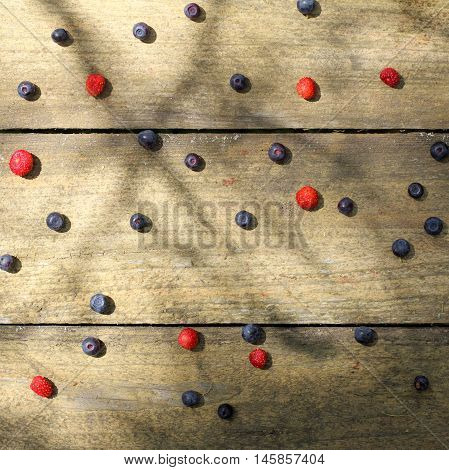 flat layout berries spilling forest blueberries and strawberries on old wooden surface top view / wild berries sifting of the randomly