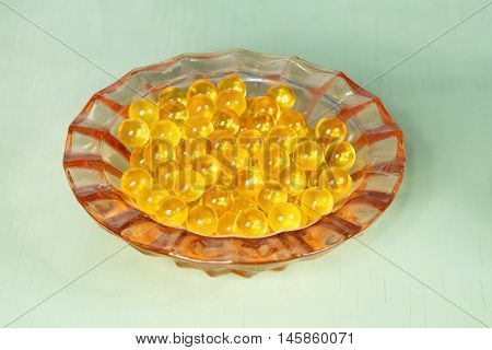 Cod liver oil capsules. On a green background