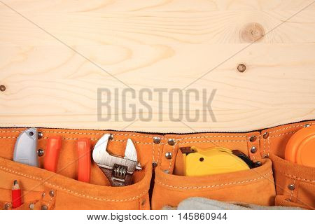 Suede orange belt with pliers, red pencil, work gloves and other tools isolated on a wooden background