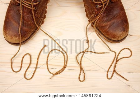 Pair of work boots. There written the word 'work' by laces on wooden background