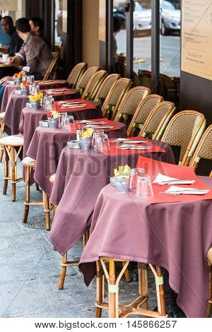 Paris France - August 25 2015: Traditional cafe in Paris with open terrace round tables and wicker chairs France