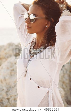 Beautiful boho styled girl wearing white shirt with flash tattoo at the beach in sunlight