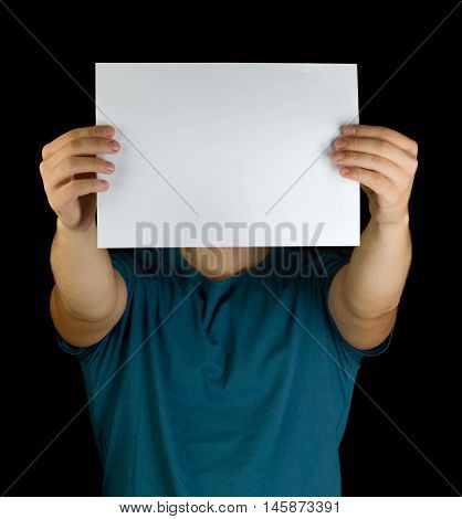 young man holding white blank paper on extended hands copy space advertisement in front of his face isolated on black