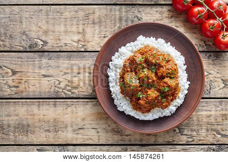 Traditional Madras butter Beef spicy slow cook lamb food with rice in clay dish on vintage wooden table background. Delicious India culture restaurant dish.