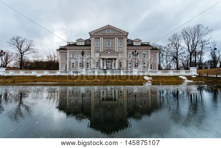 Large mansion or house stands on the former site of the fortress with a moat. Front of the house is reflected in the water.