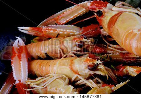 Delicious Roasted Langoustines with Thyme and Rosemary closeup in Frying Pan. Focus on Animal Eyes