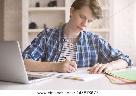 Close up of casual young man working on coursework at desk with blurry laptop. White brick wall and shelves in the background