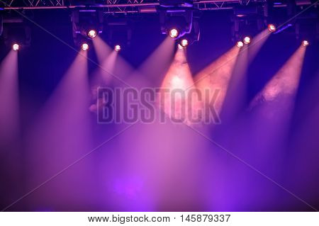 Purple stage spotlights hanging on lighting pipe systems
