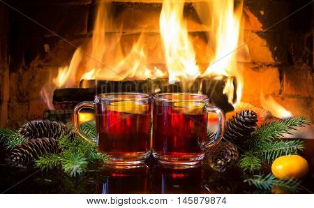 Christmas New Year composition. Two glasses of mulled red wine or hot drink tea with christmas decoration - fir branches in front of warm fireplace. Romantic, relaxed magical atmosphere near fireplace