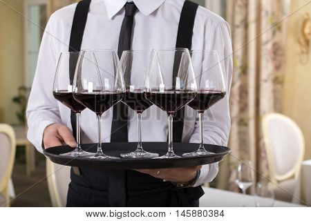 red wine glasses on a tray waiter tray with white wine a lot of glasses
