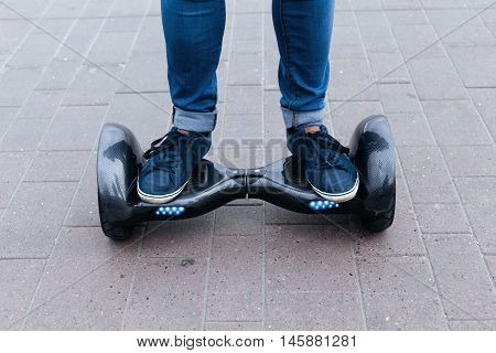 The man in blue jeans and sneakers rides a blue electric scooter, hoverboard, gyroboard or gyroscooter. Two feet standing on a platform