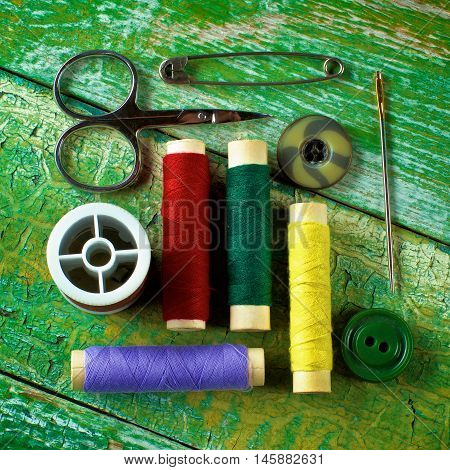 Arrangement of Various Spools of Thread Scissors Pins Needles and Buttons closeup on Cracked Wooden background