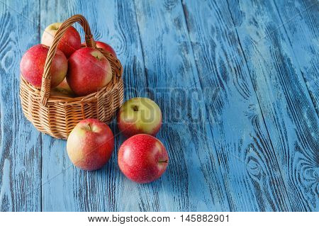 Wicker Basket Full Of Red Gala Apples On Rustic Wooden Background