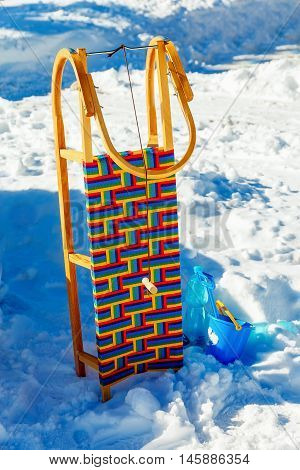 Wooden sledge in the snow. Isolated on blue and white background