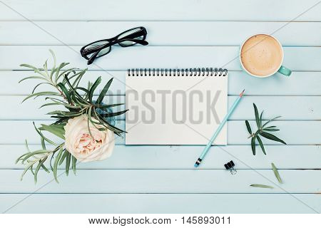 Morning coffee cup, clean notebook, pencil, eyeglasses and vintage rose flower in vase on blue rustic desk overhead view. Planning and design concept. Cozy breakfast. Flat lay styling.