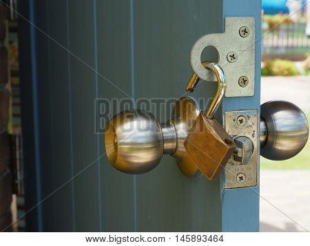 Padlock hangs on the opened wooden door poster