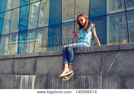 City lifestyle stylish youth using a smartphone sitting against the business on a sunny summer day