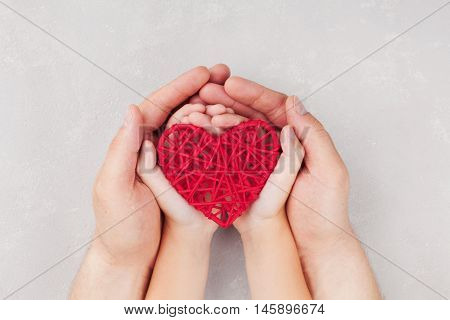 Adult and child holding red heart in hands top view. Family relationships health care pediatric cardiology concept.