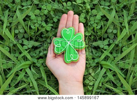 Woman holding decorative cookie. Saint Patrics Day concept