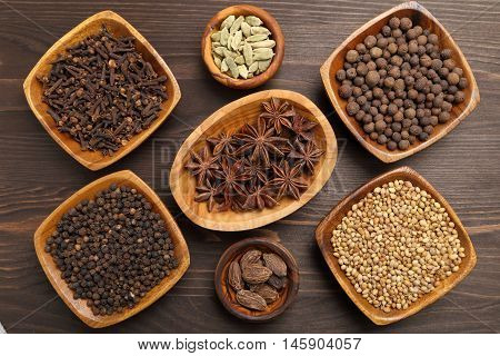 Aromatic spices and herbs in wooden bowls.