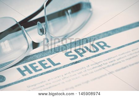 Heel Spur - Medical Concept with Blurred Text and Pair of Spectacles on Blue Background. Selective Focus. 3D Rendering.