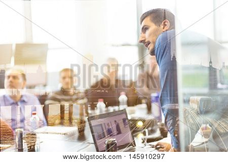 Business man making a presentation at office. Business executive delivering a presentation to his colleagues during meeting, explaining business plans to his employees. City reflection in window.