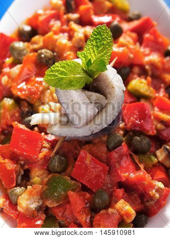 Tunisian salad with red peppers marinated fish and capers. Close up vertical shot