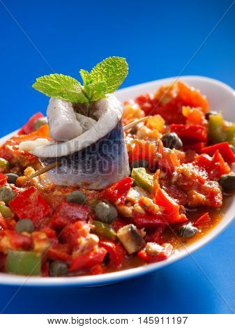 Tunisian salad with red peppers marinated fish and capers. Vertical shot