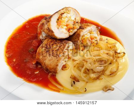 Chicken roulades stuffed with boiled eggs carrots and onion. Tomato and potatoe puree for side dish. Horizontal shot