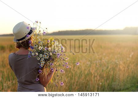 girl in a summer hat with a large bouquet of wildflowers admires the sunset / girl with wildflowers