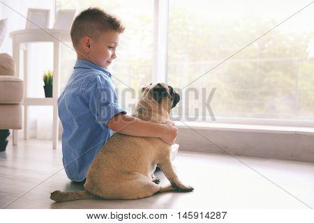 Cute boy with pug dog on floor