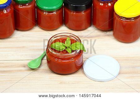 Homemade preservation of ketchup, jars of ketchup at background