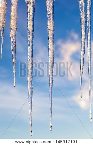 Icicles against a blue sky with clouds at sunset.