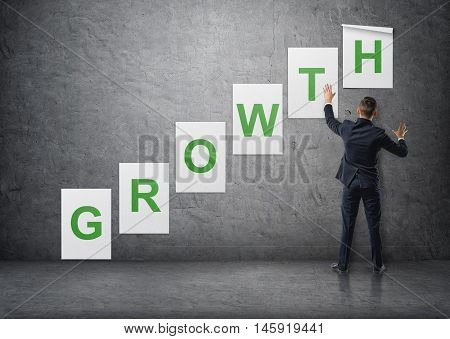 Businessman putting up posters with letters on a concrete wall that form a 'growth' word. Business staff. Office clothes. Succesful management.