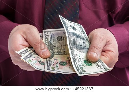 Dollar bills in the hands of a businessman in a shirt and tie.