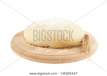 Dough for bread and wheat ears isolated on white background.
