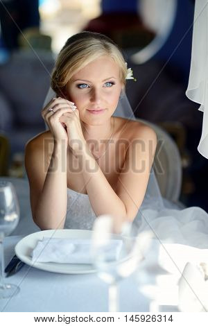 Beauty bride in bridal gown with lace veil indoors. Beautiful model girl in a white wedding dress. Female portrait of cute lady. Woman with hairstyle