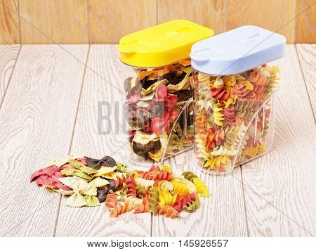raw fancy pasta of different color in plastic containers