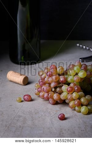 Fresh grapes with wine bottle, sommelier background. Copy space.