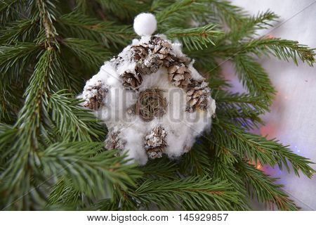 Christmas toy in the form of the house. The toy is located on a fir-tree. The house is made of fir cones and cotton
