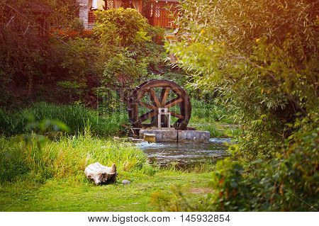 Old wooden waterwheel watermill on a horse farm. The old water wheel covered with moss. Flowing water to the mill. Old technology energy water movement