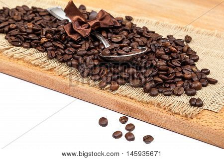 Coffee beans on sackcloth with a cupronickel spoon.