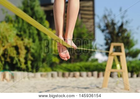 Girl walking on the sling. Child balancing on slackline at a beach. Shadow of a human figures on the sand.